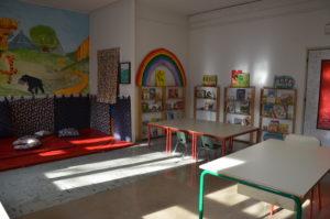 Foto biblioteca. è presenta un angolo morbido per la lettura, scaffali con libri e tavoli.