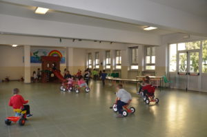 Foto grande salone per le attività di movimento e gioco libero dotato di vari giochi e di una LIM.